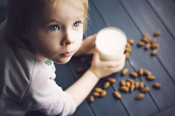 Little girl holding glass of vegan milk.