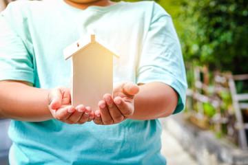 Children holding a wooden house Have money slots To save money to spend in the future