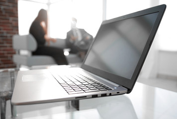 Focus on laptop on the table. Blurred people on background.