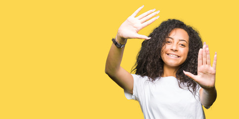 Young beautiful girl with curly hair wearing casual white t-shirt Smiling doing frame using hands palms and fingers, camera perspective