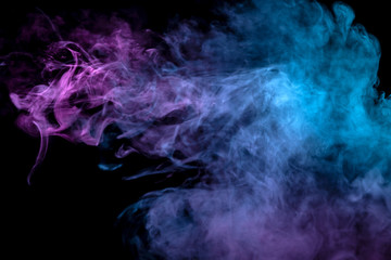 Multicolor, thick smoke, illuminated by colored in blue, purple and pink light against a dark black isolated background, welded with clubs and curls, rising from a steam of vape. Wind blow