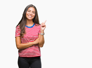 Young beautiful arab woman over isolated background with a big smile on face, pointing with hand and finger to the side looking at the camera.