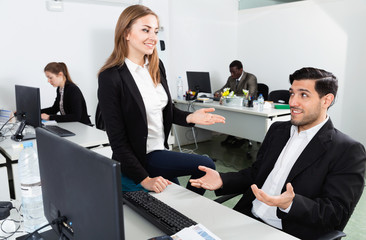 Young businesswoman flirting with Hispanic male colleague during work in modern coworking space