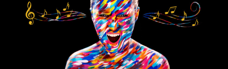 Portrait of the bright beautiful girl with art colorful make-up, bodyart and notes. Colorful paint on body.