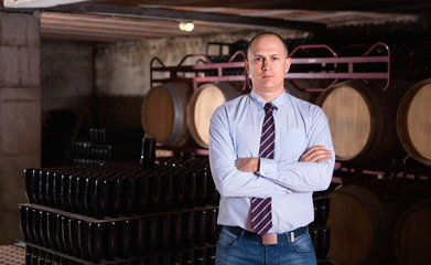 Confident succesful man winemaker posing in own winery vault
