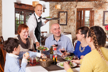 Waiter serving dishes to family