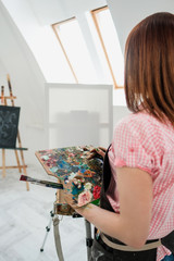 Young beautiful girl painter in a white studio draws on an easel on canvas.
