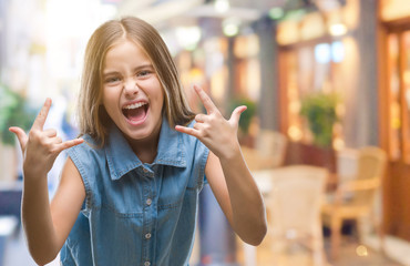 Young beautiful girl over isolated background shouting with crazy expression doing rock symbol with hands up. Music star. Heavy concept.