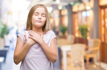 Young beautiful girl over isolated background smiling with hands on chest with closed eyes and grateful gesture on face. Health concept.