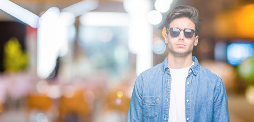 Young handsome man wearing sunglasses over isolated background skeptic and nervous, frowning upset because of problem. Negative person.