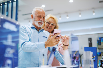 Smiling Caucasian senior couple trying out smart phone for present for granddaughter while standing in tech store.
