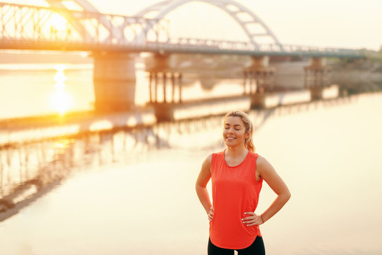Smiling Caucasian sporty woman with hands on hips resting from running. In background river, bridge and morning sun.