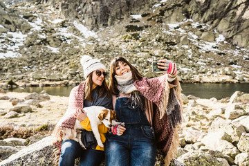 .Two young women, covered with a blanket, on a sunny winter morning enjoying a day on the mountain with their cute little dog taking themselves pictures with their smartphone. Lifestyle.
