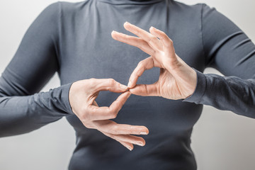 Woman learns sign language to talk. Hand gestures of people with hearing impairment.