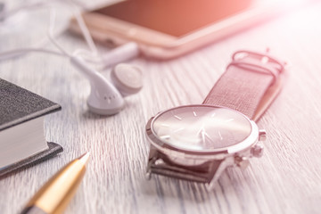Wrist watch, mobile phone with headphones and a notebook with a pen on an old white office desktop and cafe