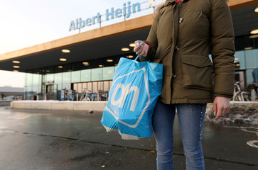 A woman holds a bag with the logo of Albert Heijn, operated by Ahold Delhaize, the Dutch-Belgian supermarket operator, in Eindhoven