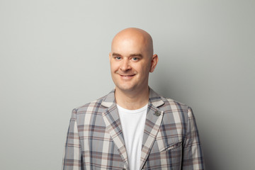 Cute bald man in a jacket and t-shirt shows against a gray wall Wall mural