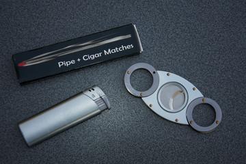 Cigar cutter, matches and cigarette lighter