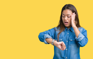 Young beautiful brunette woman wearing blue denim shirt over isolated background Looking at the watch time worried, afraid of getting late