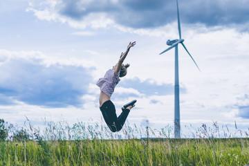 girl on a windmill background, summer windmills, sunset. Wind turbine, wind power. wind power plant