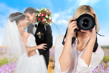 Female photographer holding camera and just married couple on