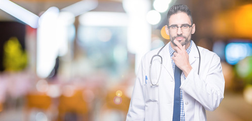 Handsome young doctor man over isolated background looking confident at the camera with smile with crossed arms and hand raised on chin. Thinking positive.