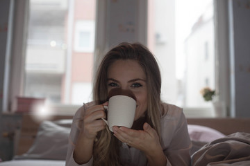 Woman Enjoying a cup of coffee in bed.