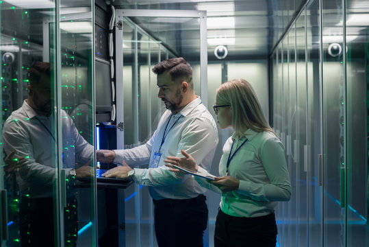 Diverse adult man and woman using tablet and laptop while diagnosing server hardware in modern data center