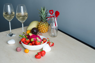Romantic dinner for two with champagne and fruits. Strawberry, champagne, pineapple, pitahaya, passion fruit, mango. Valentine's Day.