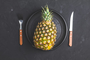 Pineapple in ceramic plate and set of cutlery knife and fork