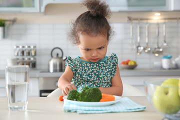 Cute African-American girl with plate of vegetables at table in kitchen