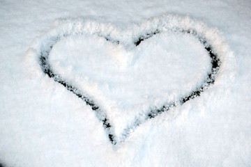 A heart is drawn on the snow. Symbol of love and Valentine's day .
