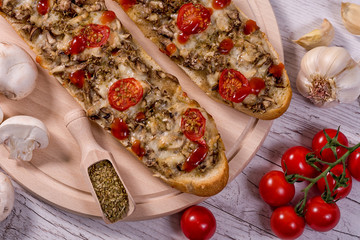 Tasty Pizza Baguette with Mushrooms and Parmesan Ingredients -paradaya, salad, garlic, oregano, olive oil on a wooden table traditional Italian food
