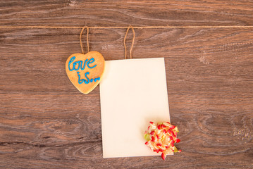 Ginger heart with a postcard and a flower on a wooden background