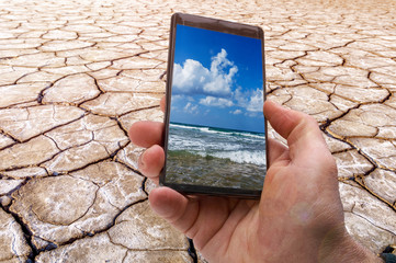 environmental concept, photo on the smartphone of the clear blue sea on the background of the cracked earth. Nature preservation.