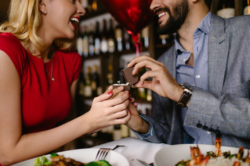 Handsome man proposing a beautiful woman to marry him in restaurant during date.
