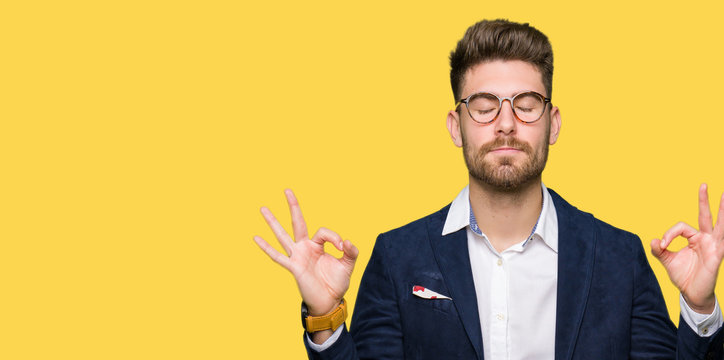 Young handsome business man wearing glasses relax and smiling with eyes closed doing meditation gesture with fingers. Yoga concept.