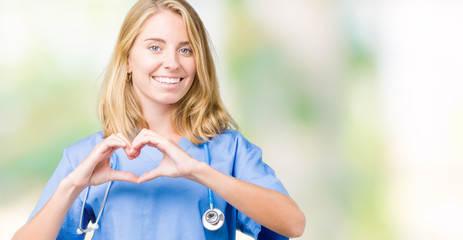Beautiful young doctor woman wearing medical uniform over isolated background smiling in love showing heart symbol and shape with hands. Romantic concept.