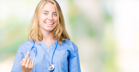 Beautiful young doctor woman wearing medical uniform over isolated background Beckoning come here gesture with hand inviting happy and smiling
