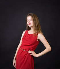 A beautiful girl in a red dress with long hair and a make-up.