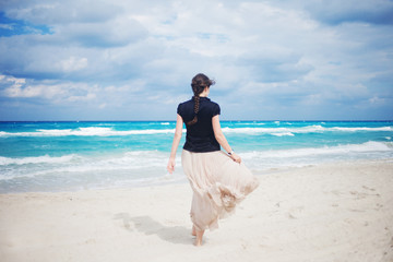 Back view of young woman in a long skirt walking on the ocean.
