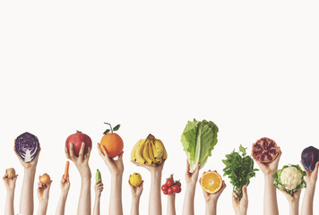 Hands holding different vegetables and fruit on isolated background