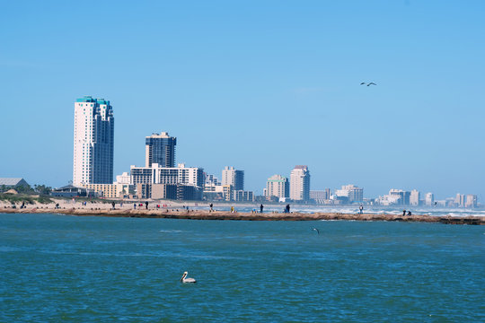 View of the skyscrapers, hotels, recreation areas of South Padre Island and the pier with fishermen a resort town on a barrier island of the same name, off the southern coast of Texas