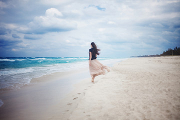 young woman in a long skirt walking on the ocean.