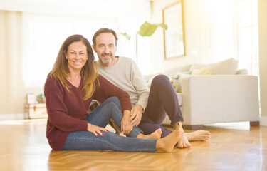 Beautiful romantic couple sitting together on the floor with the cat at home