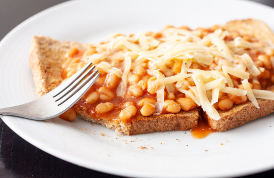 Partially eaten meal of baked beans on toast topped with grated cheese