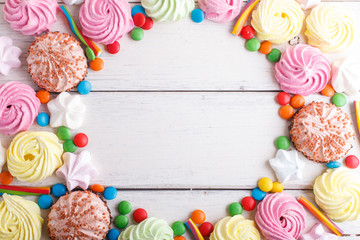Colorful frame of multicolored candies on white wooden background.