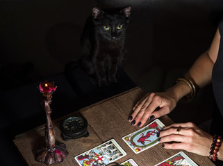 The fortune teller lays out on a wooden table the tarot cards by the light of a lantern and a candle. Black cat sitting near the table. Selective focus.