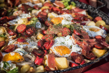 Baked eggs with chorizo, jamon and bacon in the pan. close up selective focus4