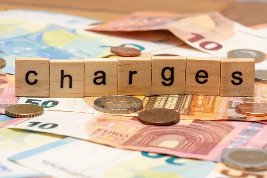 """Lettres en bois composant le mot """"charges"""" sur fond de billets de banque et de pièces"""
